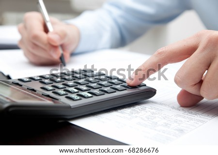 A businessman doing some paperwork using his calculator
