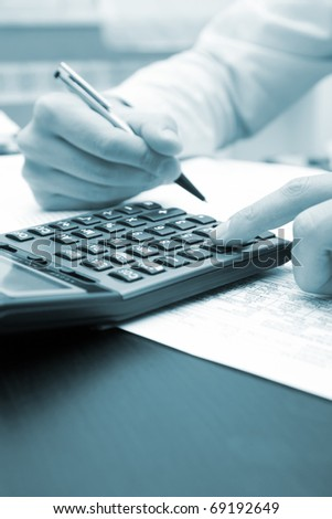 A businessman doing some paperwork using his calculator - blue toned image - stock photo