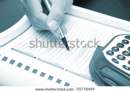A businessman doing some paperwork using his calculator - blue toned image