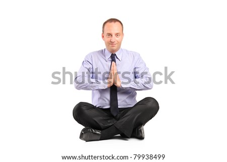 A businessman doing yoga exercise seated on a floor isolated on white background