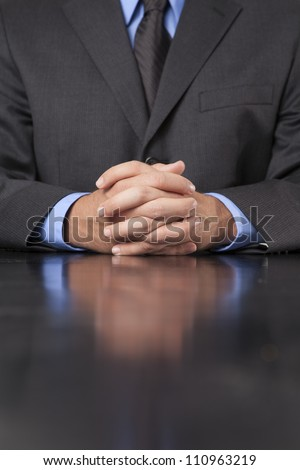 A businessman dressed in a suit sits at a desk with his hands clasped showing power and confidence. - stock photo