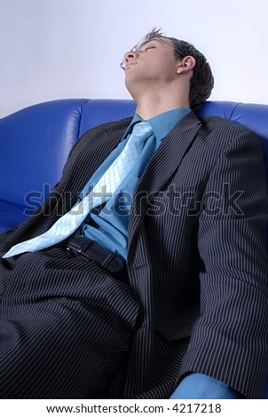 A businessman dressed in suit felt asleep on blue leather sofa.