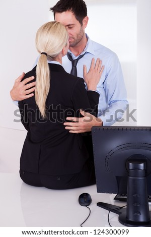 A businessman embraces a female colleague who is sitting on a desktop as mutual passion leads to an affair or love in the workplace - stock photo