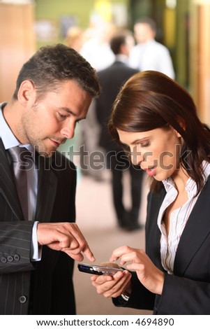 A businessman explains how to use a cellphone as an appointment calendar to his female partner. - stock photo