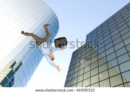A businessman falls from a building rooftop after too much emotional stress at work caused him to commit suicide. - stock photo
