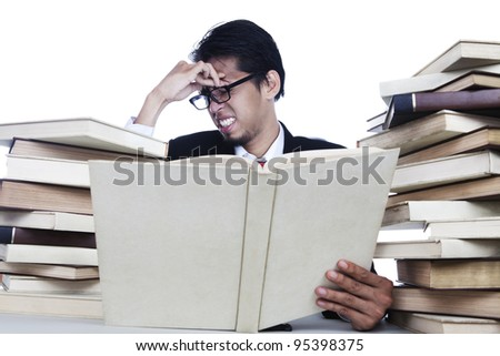 A businessman having headache after read books - stock photo