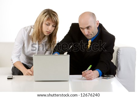 A businessman helping a young woman set up her laptop computer