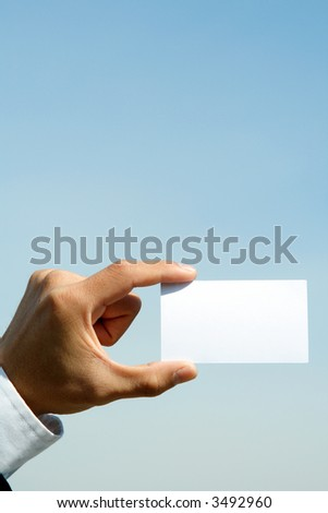 A businessman holding a blank business card outdoor - stock photo