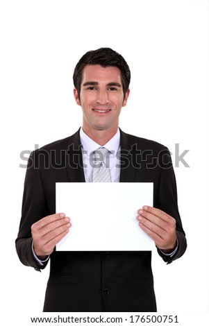 A businessman holding a blank poster. - stock photo