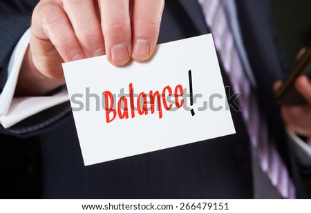 A businessman holding a business card with the words, Balance, written on it.