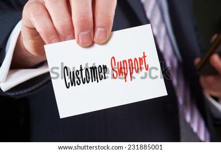 A businessman holding a business card with the words, Customer Support, written on it. - stock photo