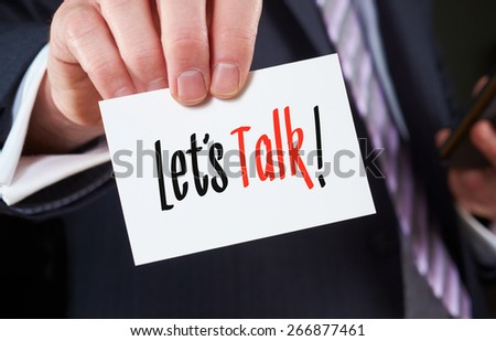A businessman holding a business card with the words, Let's Talk, written on it. - stock photo