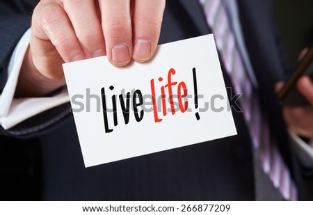 A businessman holding a business card with the words, Live Life, written on it. - stock photo