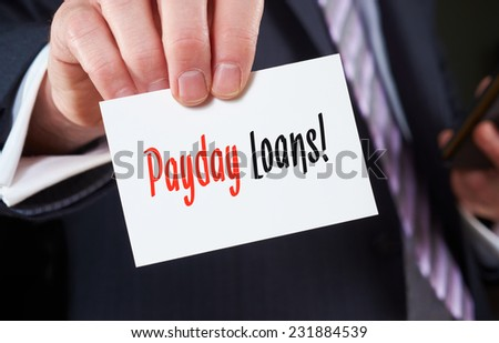 A businessman holding a business card with the words, Payday Loans, written on it. - stock photo