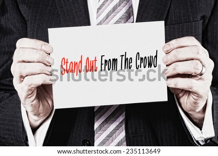 A businessman holding a business card with the words, Stand Out From The Crowd, written on it. - stock photo