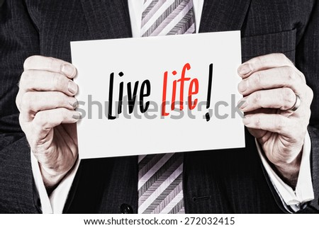 A businessman holding a card with the words, Live Life, written on it. - stock photo