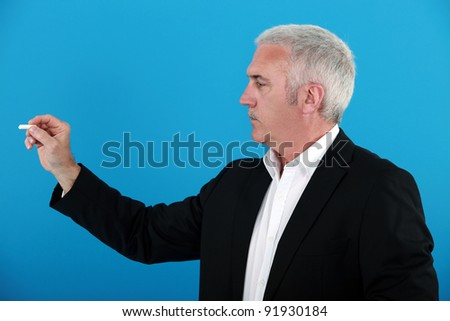 A businessman holding a chalk. - stock photo
