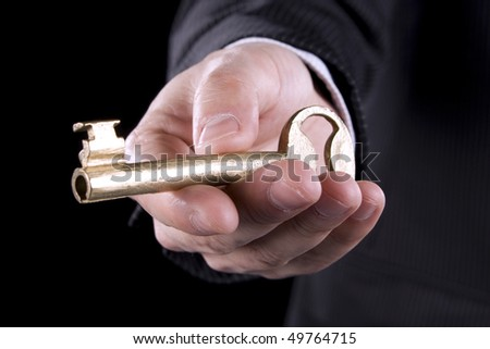 A businessman holding a golden key - stock photo