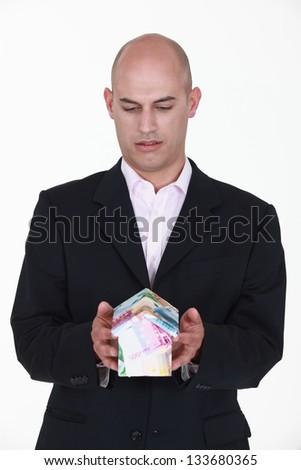 A businessman holding a miniature house made out of bills. - stock photo