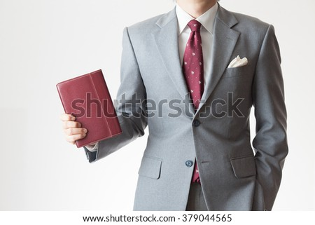 A businessman holding a schedule book