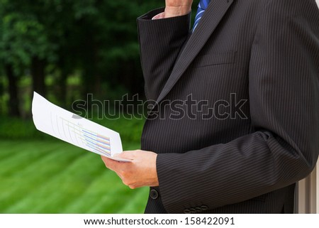 A businessman holding a sheet of paper with a graph