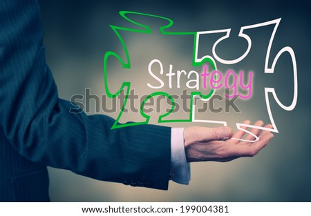 A Businessman holding a strategy puzzle concept. - stock photo
