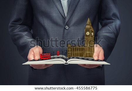 A businessman holding an open book with a sketch of London on the top of it. Big Ben, Palace of Westminster. Double-decker bus.. City of London. Leading global city in finance and business. - stock photo