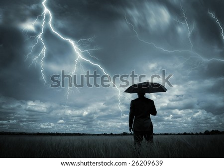 A businessman holding an umbrella in a storm. - stock photo