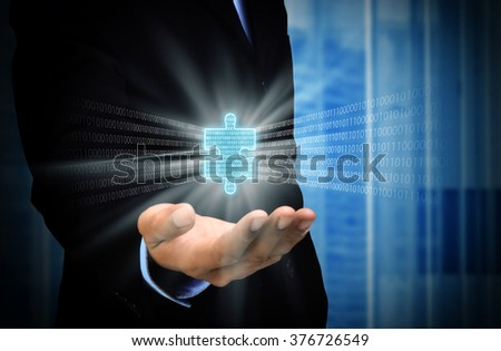 A businessman holding  and showing an important piece of digital information puzzle