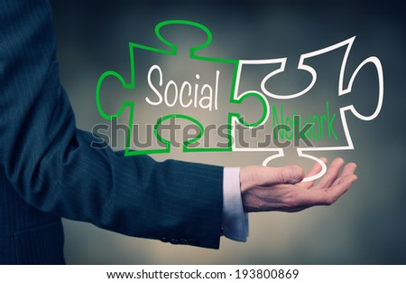 A Businessman holding at a social network puzzle concept. - stock photo