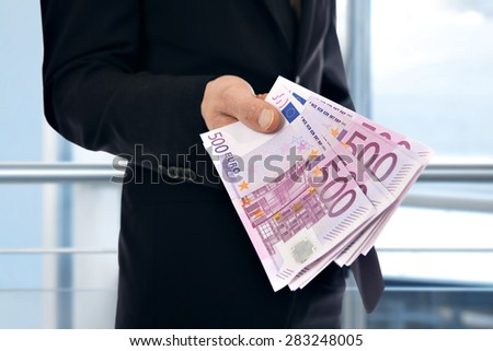 A businessman holding money - Euro (EUR)
