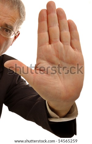 A businessman holding up his hand in a stop sign. - stock photo