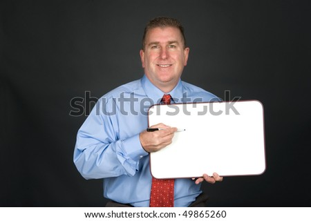 A businessman holds a blank whiteboard to explain his communication needs.  Board left blank for designers to add ccopy space.