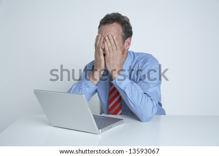 A businessman holds his head in his hands in desperation - stock photo
