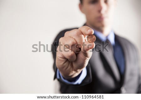 A businessman holds up a penny on a white background showing savings and earnings. - stock photo