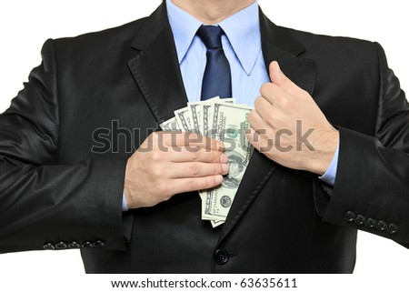 A businessman in a black suit putting money in his pocket isolated on white background - stock photo