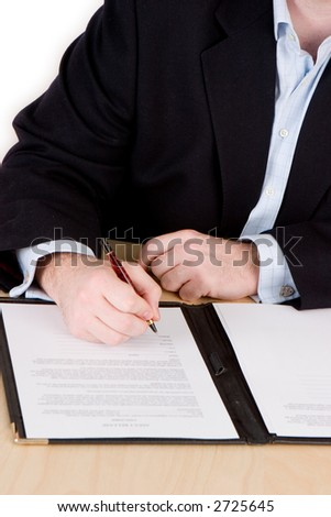 A businessman in a blue suit and no tie signing a contract