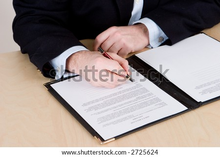 A businessman in a blue suit signing a contract on a wooden table