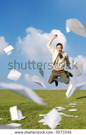 A businessman in a field jumping with his paperwork flying around him. - stock photo