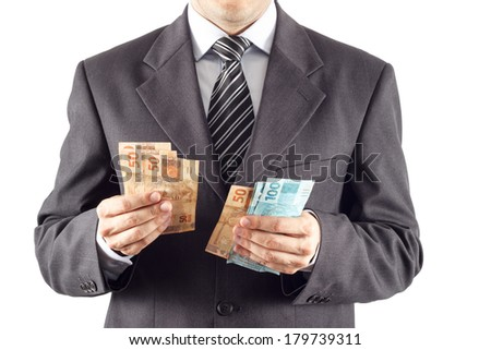 A businessman in a suit counting brazilian money - stock photo
