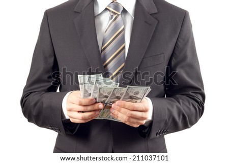 A businessman in a suit counting new hundred dollar bills - stock photo