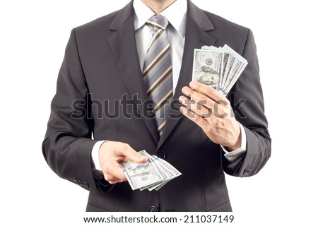 A businessman in a suit giving new dollar money