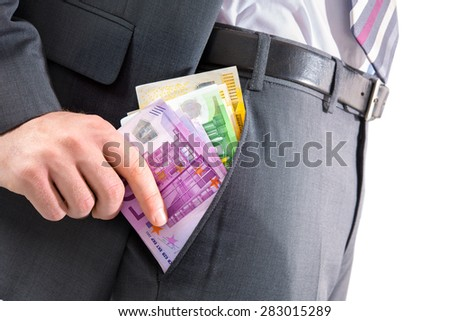 A businessman in a suit putting money in his pants pocket - stock photo