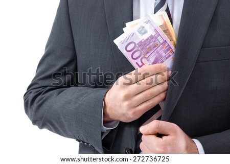 A businessman in a suit putting money in his pocket - stock photo