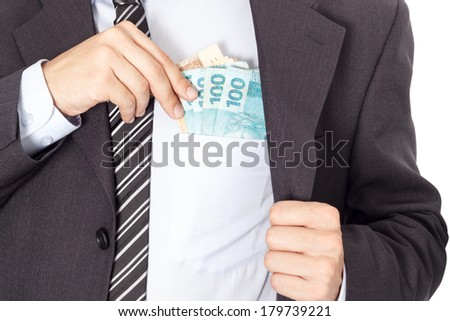 A businessman in a suit putting money in his pocket isolated on white background