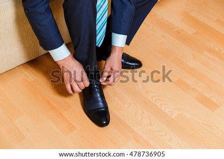 A businessman in blue suit and tie tying his shoelaces