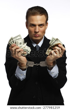 A businessman in handcuffs holding dollars  - stock photo