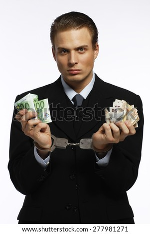 A businessman in handcuffs holding euro banknotes - stock photo