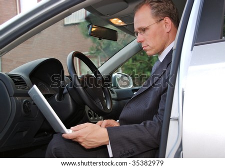 A businessman in his car is checking his email on his white laptop