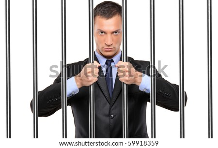 A businessman in jail holding bars isolated on white - stock photo